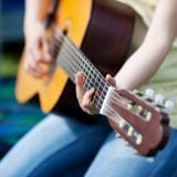 Young girl making music and playing guitar