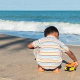 Cute little boy play toy car on the beach alone