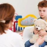 Red-haired, autistic boy with teddy bear concentrated on his therapist