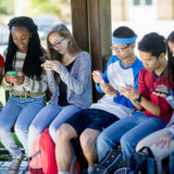 A multi-ethnic group of high school teenagers are sitting outside and are texting on their cell phones before class.