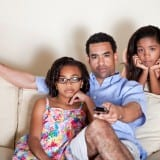Dad watching TV with daughters