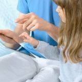 child and parent looking at ipad