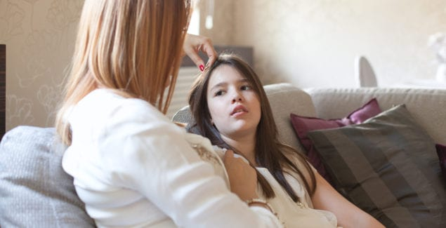 Mother sits next to daughter on sofa stroking her hair