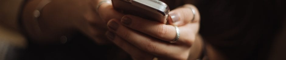Closeup of young girls hands cupping a gripping a smartphone