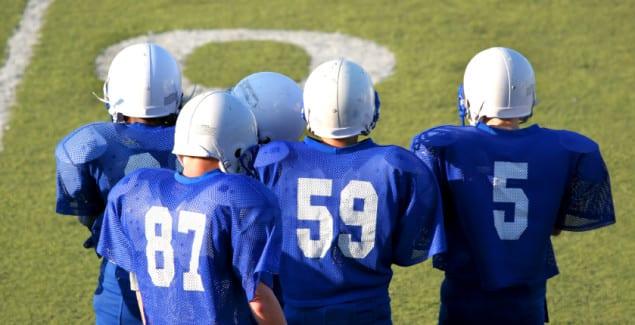 Teens banging in football gear