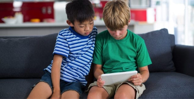 Two grade school-age siblings using a digital tablet on the couch