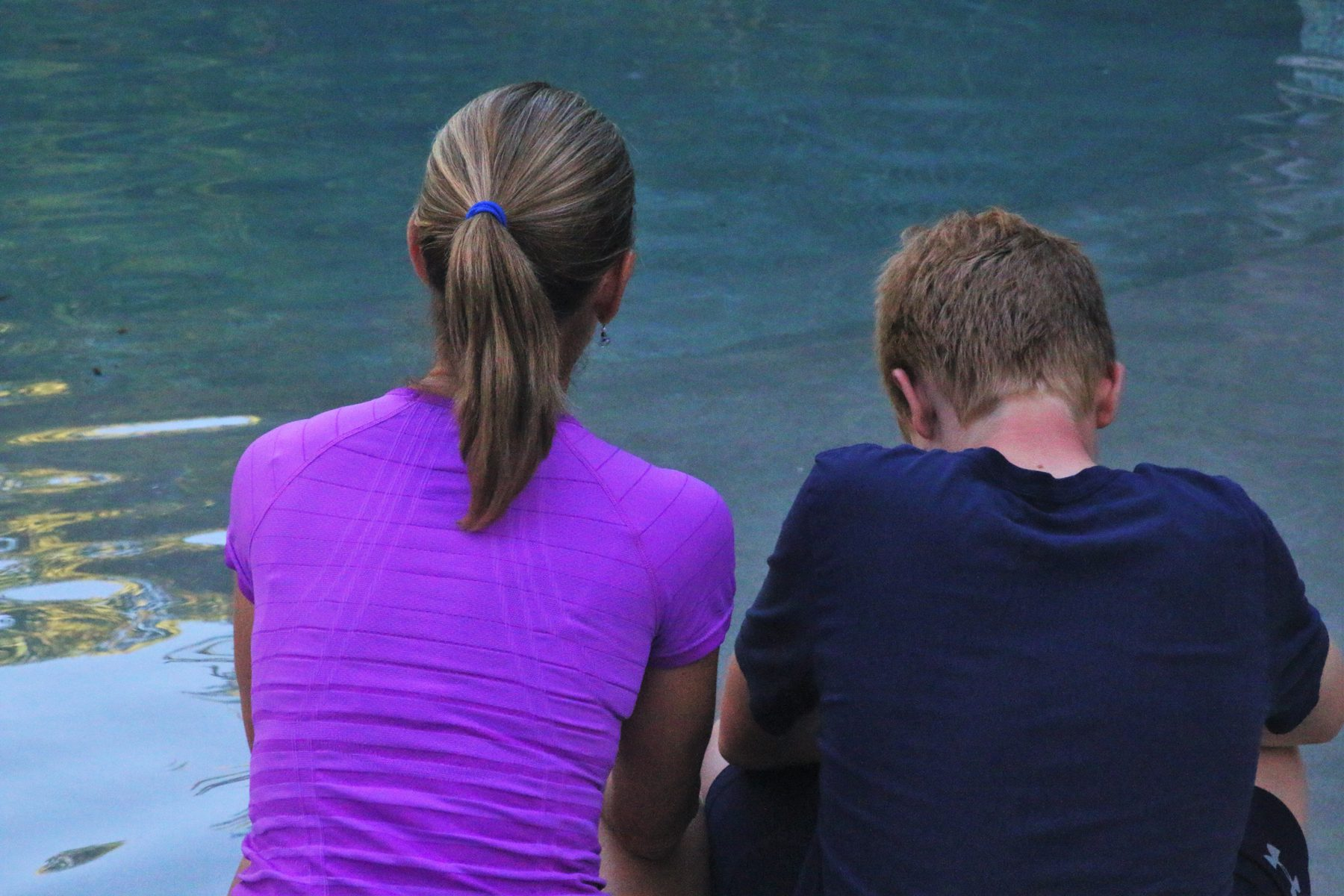 Behind shot of parent and teen sitting in front of water, talking